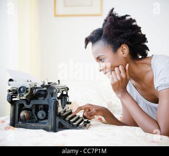 Black woman using old-fashioned typewriter