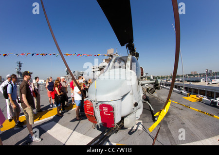 Visitors admire a Marine Corps AH-1W Super Cobra helicopter on the flight deck of the Iwo Jima during Fleet Week - Stock Photo