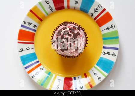 looking down on Strawberry cupcake with heart shaped chocolates sprinkled on top placed on colourful yellow plate - Stock Photo