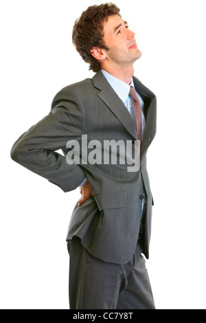 Young businessman holding his hand at his aching back isolated on white - Stock Photo