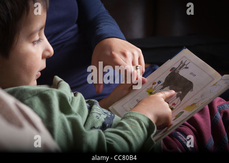 Mother teaches 3 years old boy to read Stock Photo