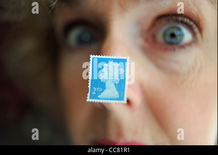 Middle aged woman close up face with a British second 2nd class postage stamp stuck to nose model - Stock Photo