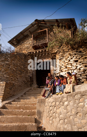 India, Arunachal Pradesh, Dirang Dzong, young people sat on steps at entrance to historic fortified village - Stock Photo