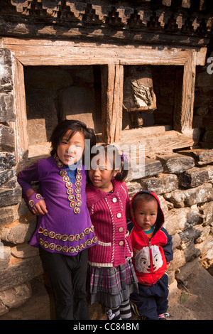 India, Arunachal Pradesh, Dirang Dzong, children at entrance to historic fortified village beside old prayer wheel - Stock Photo
