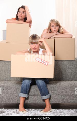 Three housemates with boxes - Stock Photo