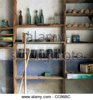 Old bottles, wooden shoes, and other items on a shelf in an abandoned farmhouse, Limousin, France - Stock Photo