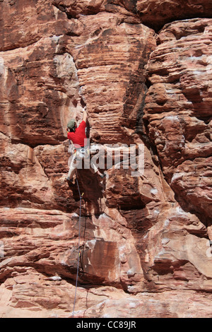 a male rock climber in red leads on a sandstone cliff at Red Rocks, Nevada - Stock Photo