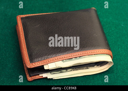 a leather wallet filled with US bills on a green felt background - Stock Photo