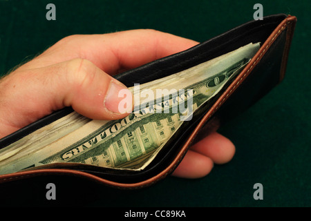 a man's hand holds a leather wallet filled with US bills open on a green background - Stock Photo