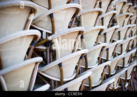 Stacked chairs in front of a bar cafe at dawn in Nice, France - Stock Photo