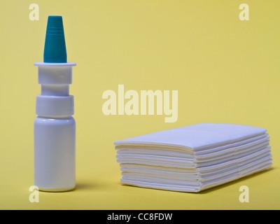 ein Nasenspray, daneben liegen Taschentücher   a nasal spray, beside are handkerchiefs - Stock Photo