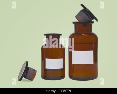 Detail photo of two pharmacists bottles, one is half opened and one is closed - Stock Photo