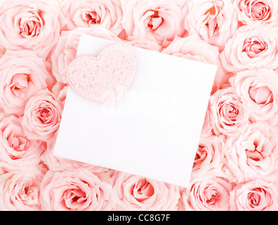 Pink fresh roses background with heart & isolated blank greeting card, love concept - Stock Photo