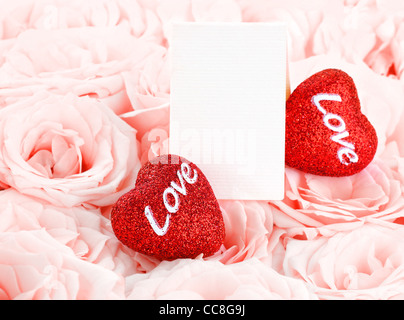 Pink fresh roses background with red hearts & blank greeting card, love concept - Stock Photo