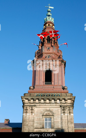 Danish flags in the tower windows of Christiansborg Palace, the parliament building in Copenhagen, Denmark, in celebration. - Stock Photo