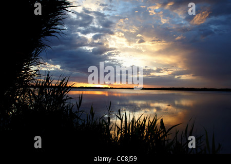 Sunrise on like and clouds - Stock Photo