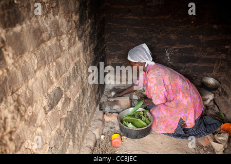 A woman cooks over an open stove in Masaka, Uganda, East Africa - Stock Photo