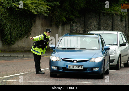 Armed female PSNI officer directing traffic in Londonderry, Northern Ireland, UK - Stock Photo