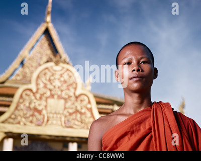 Young Asian monk smiling at camera in buddhist monastery, Phnom Penh, Cambodia, Asia. Low angle - Stock Photo