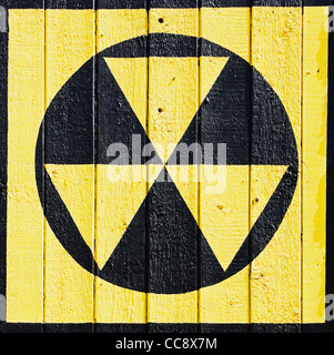 radiation symbol painted on wooden wall - Stock Photo