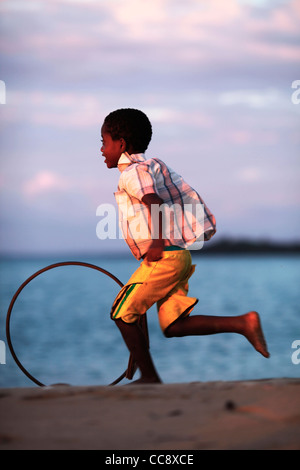 A local young malagasy african boy 6-10 years running with a stick and a bicycle rim, a traditional toy. Nosy Komba, - Stock Photo