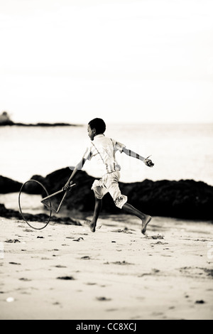 A young malagasy boy 6-10 years running with a stick and a bicycle rim, a traditional toy, at the beach. Nosy Komba, - Stock Photo