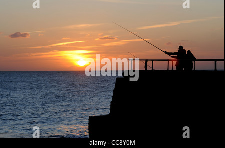 A fisherman catches the last of the sun at dusk on Brighton seafront this afternoon Photograph taken by Simon Dack - Stock Photo