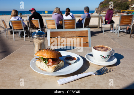 Breakfast at Tamarama Beach Sydney with coffee and sandwich. Outside on table with people in the background - Stock Photo