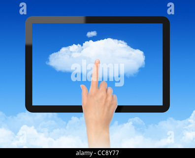 Woman hand touch the cloud against blue sky with clouds. Concept image on cloud computing theme. - Stock Photo