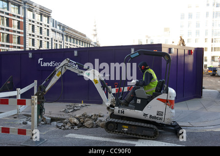 workman using mini bobcat digger digging up city of london streets London England UK United kingdom - Stock Photo