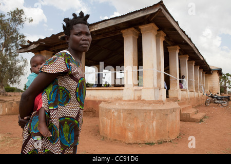 A mother carries her young child to a health centre in Kumi, Uganda, East Africa. - Stock Photo