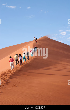 Tourists climbing Dune 45 in Namibia - Stock Photo