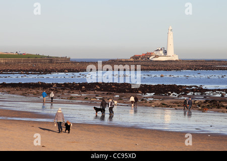 People exercising dogs on the beach at Whitley Bay north east England, UK with St Mary's Island in the background - Stock Photo