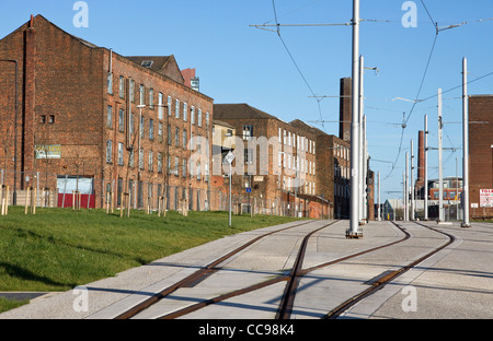 New Metrolink East Manchester Line line to Ashton passes old cotton mills (Chapeltown St ), Ancoats area , Manchester,UK - Stock Photo