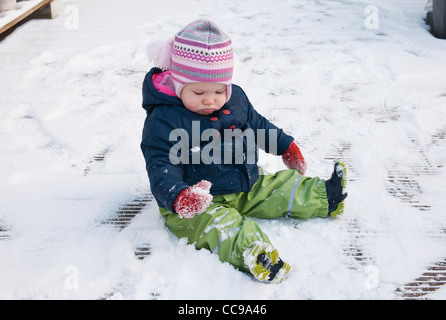 Baby Girl wearing Snow Suit sitting on Ground in Snow - Stock Photo