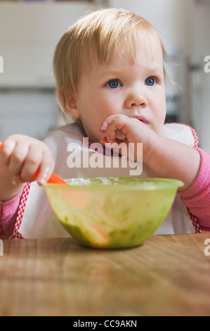 Baby Girl Eating from Bowl - Stock Photo