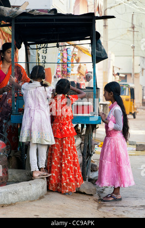 Young Indian girls buy dosa for breakfast from a cart in an Indian street. Puttaparthi, Andhra Pradesh, India - Stock Photo