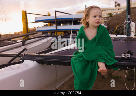 Portrait of Young Girl Wrapped in Towel Sitting on Mast of Sailboat - Stock Photo
