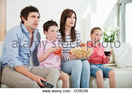 Family intently watching movie on sofa - Stock Photo