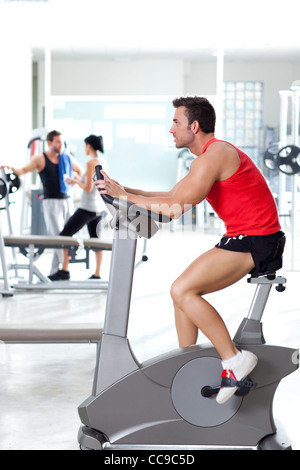 man on stationary bicycle at sport fitness gym interior - Stock Photo