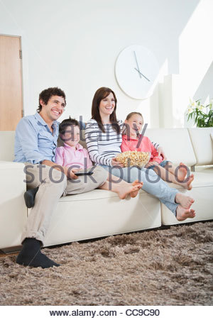Smiling family watching TV on sofa - Stock Photo