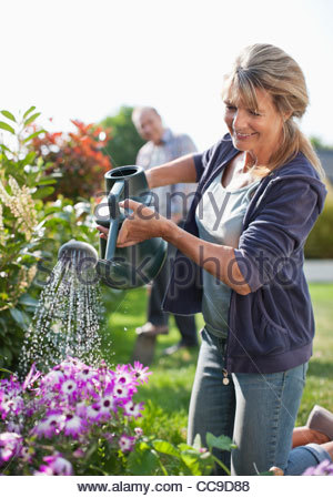 Senior woman watering flowers in garden with watering can - Stock Photo