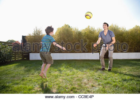 Father and son playing soccer in backyard - Stock Photo