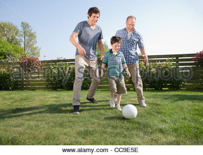 Multi-generation family playing soccer in backyard - Stock Photo