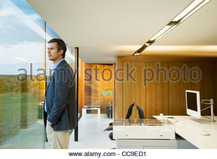 Pensive businessman looking out window in office - Stock Photo
