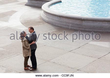 Couple hugging face to face near urban fountain - Stock Photo