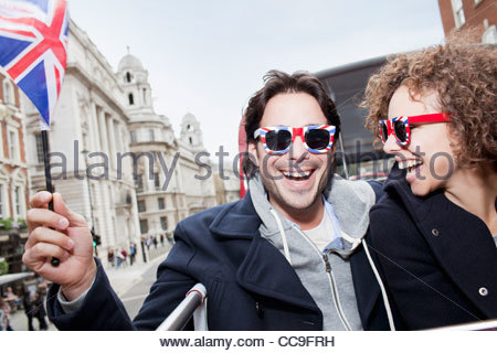 Portrait of exuberant couple with British flag and sunglasses riding double decker bus - Stock Photo