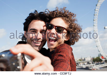 Happy couple taking self-portrait with digital camera near London Eye - Stock Photo