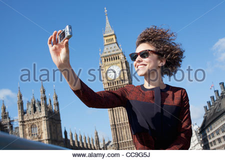 Smiling woman taking self-portrait with digital camera below Big Ben clocktower - Stock Photo