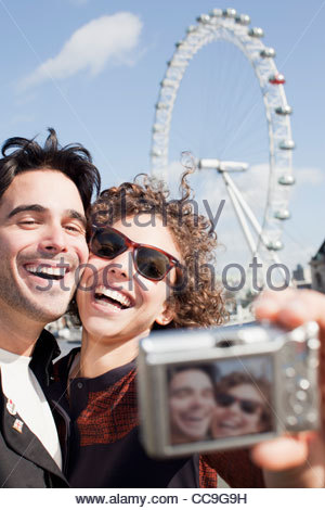 Happy couple taking self-portrait with digital camera in front of London Eye - Stock Photo